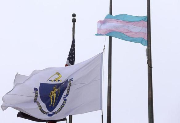 A flag representing the transgender community, right, flies next to the Massachusetts state flag, left, in Boston.